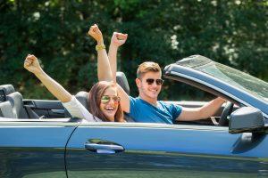 Pärchen mit Sonnenbrillen, die im Cabrio sitzen und die Arme in die Luft strecken.