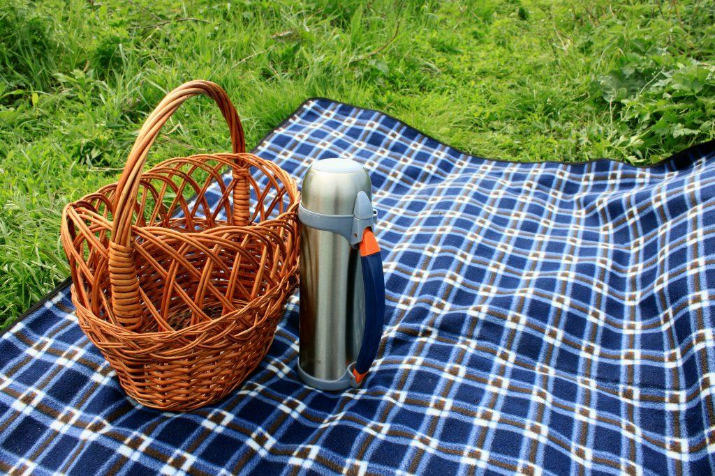 Korb, Thermosflasche und Picknickdecke auf dem grünen Gras im Sommer