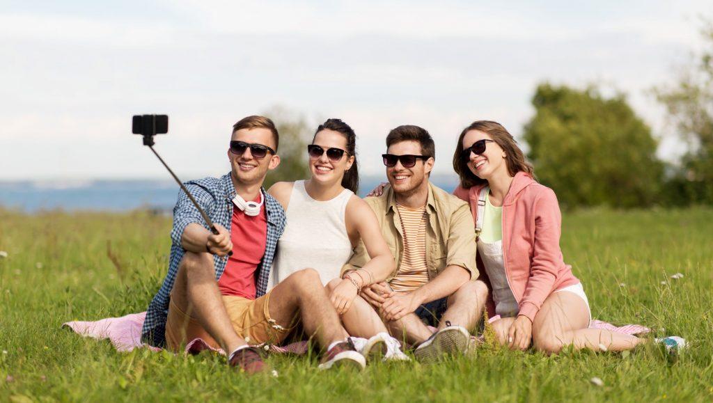 Freunde beim Selfi, sitzen auf einer Wiese.