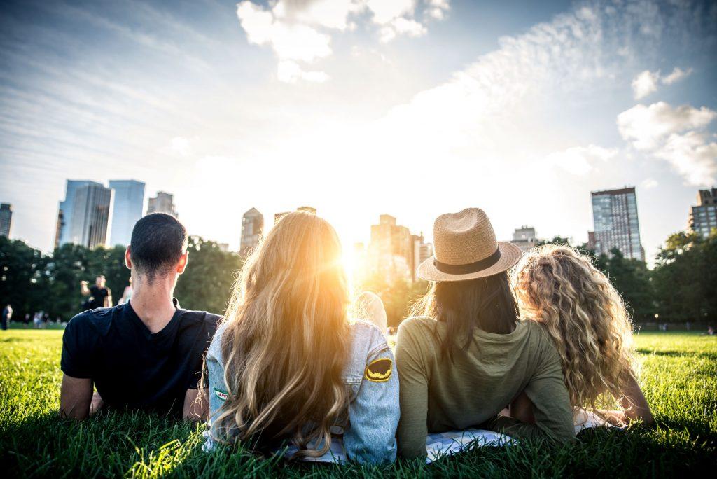 Freunde liegen auf einer Wiese und blicken auf die Stadt