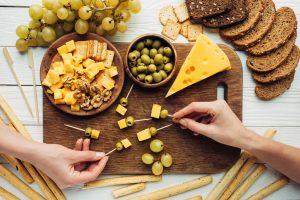 Vorbereitung von Käsespießen mit Oliven, Trauben und Kräckern