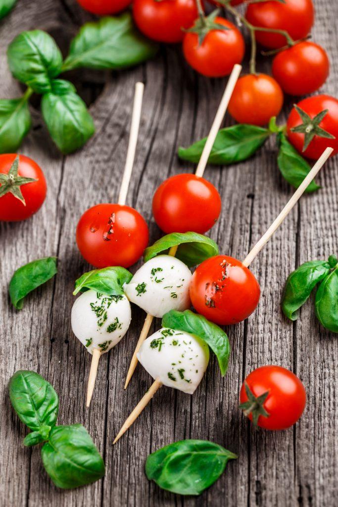 Spieße mit Tomate, Basilikum und Mozzarella auf einem rustikalen Hintergrund